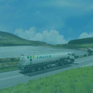 Talick tanker driving alongside a lake